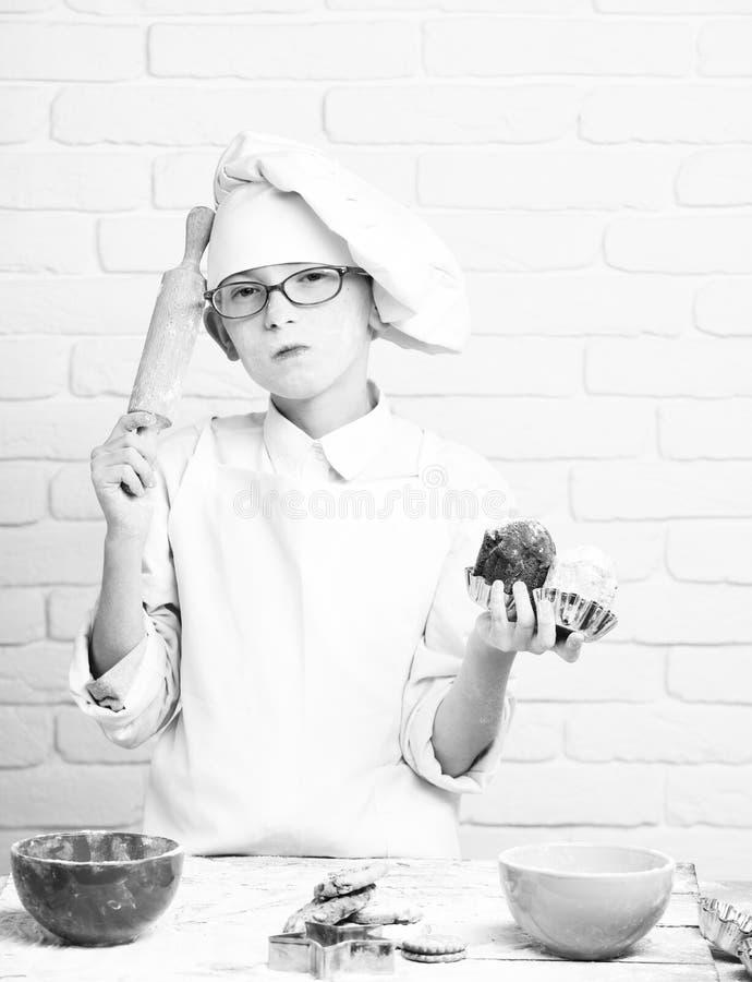 Cuoco unico sveglio del cuoco del giovane ragazzo in uniforme e cappello di bianco sulla farina macchiata del fronte con i vetri  fotografia stock