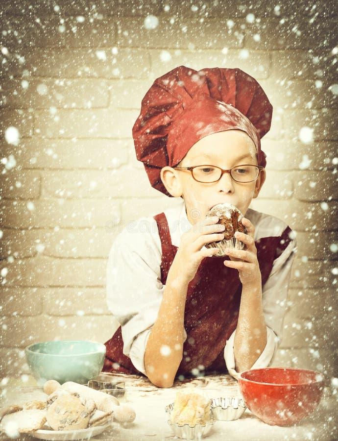 Cuoco unico sveglio del cuoco del giovane ragazzo in uniforme e cappello di rosso sul fronte macchiato con i vetri che si siedono fotografie stock
