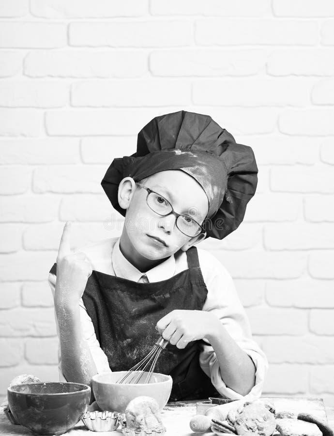 Cuoco unico sveglio del cuoco del giovane ragazzo in uniforme e cappello di rosso sul fronte macchiato con i vetri che si siedono immagine stock libera da diritti