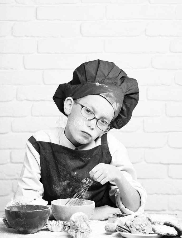 Cuoco unico sveglio del cuoco del giovane ragazzo in uniforme e cappello di rosso sul fronte macchiato con i vetri che si siedono fotografia stock libera da diritti