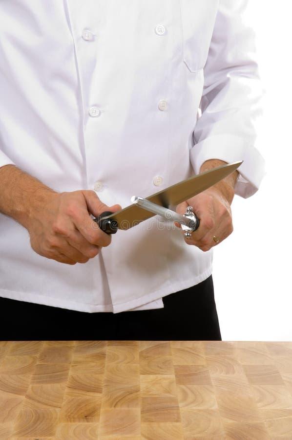 Cuoco unico - uomo che affila lama immagine stock libera da diritti