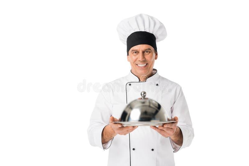 Cuoco unico in vassoio della tenuta del blanche del toque e dell'uniforme con la copertura fotografie stock