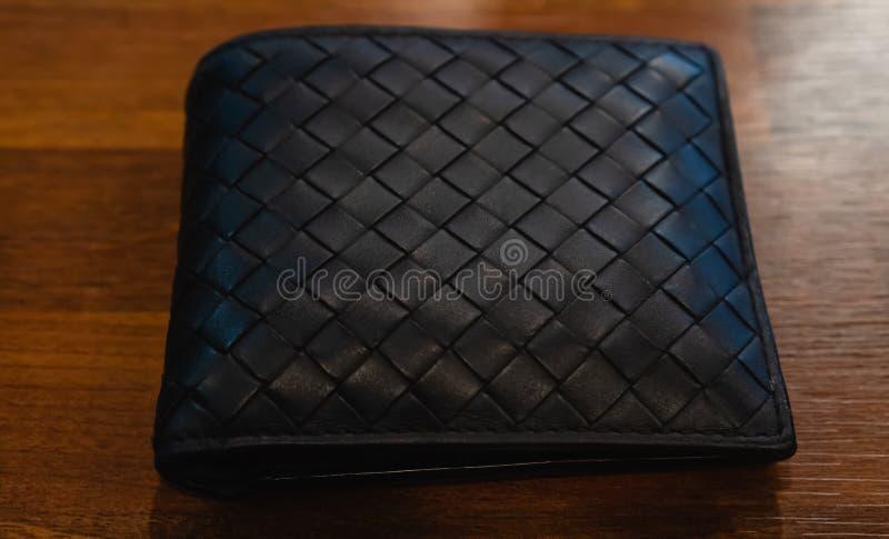 Cuoio di cuoio del nero del portafoglio sui precedenti di legno fotografia stock libera da diritti