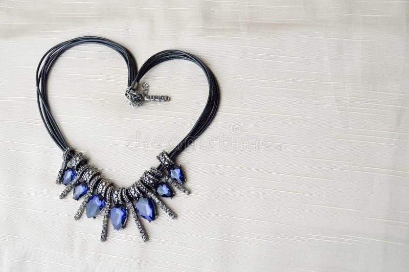 Cuore al giorno del ` s del biglietto di S. Valentino da una bella, collana femminile e alla moda su un elastico nero con le gemm fotografia stock libera da diritti