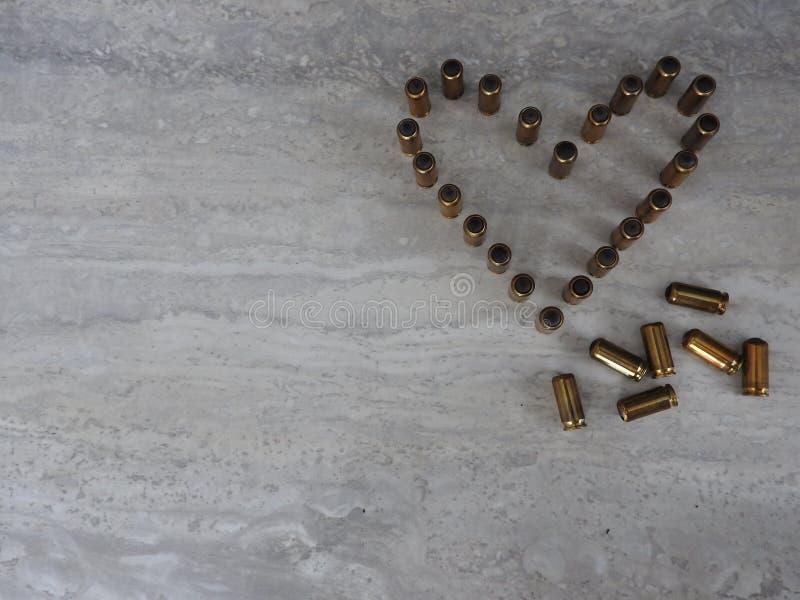Cuore allineato con le pallottole su un fondo leggero, tema di amore della festa fotografia stock