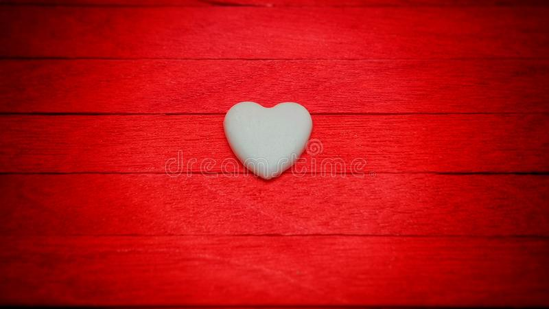 cuore bianco sul fondo di legno rosso della sfuocatura di pendenza fotografia stock