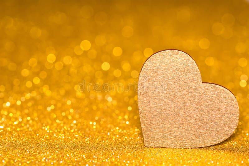 Cuore brillante su un fondo radiante dorato Lustro di scintillio con forma 3d fotografie stock