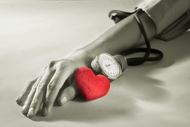 Cuore con il braccio della donna che controlla pressione sanguigna fotografia stock libera da diritti