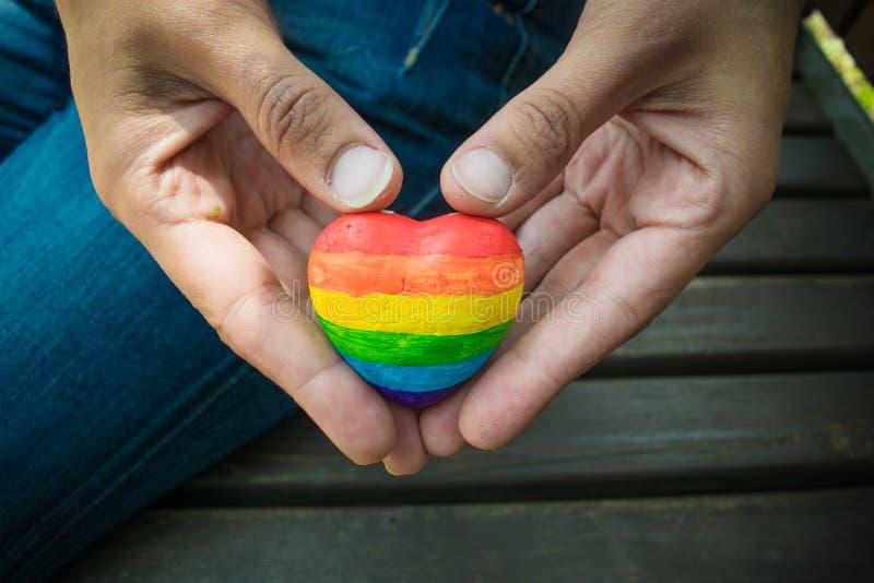 Cuore decorativo con le bande dell'arcobaleno in mani femminili Bandiera di orgoglio di LGBT, simbolo di lesbico, gay, bisessuale fotografia stock libera da diritti