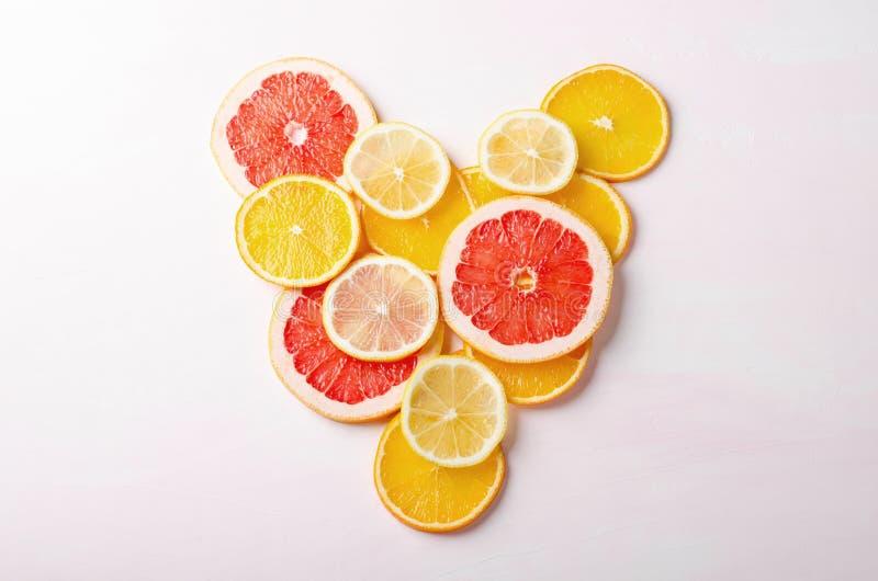 Cuore degli agrumi dalle fette di limone, arancia, pompelmo su fondo bianco Amore, sano, concetto di ecologia immagine stock libera da diritti