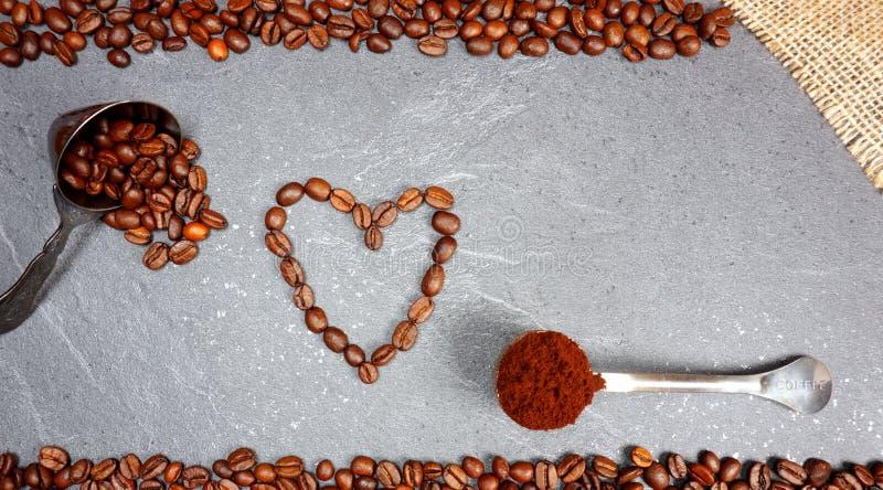 Cuore dei chicchi di caffè dai fagioli del commercio equo e solidale con il cucchiaio al fondo grigio di piano di lavoro della cu fotografia stock libera da diritti