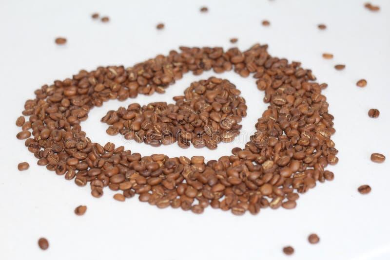 Cuore dei chicchi di caffè I chicchi di caffè sono sparsi fotografia stock libera da diritti