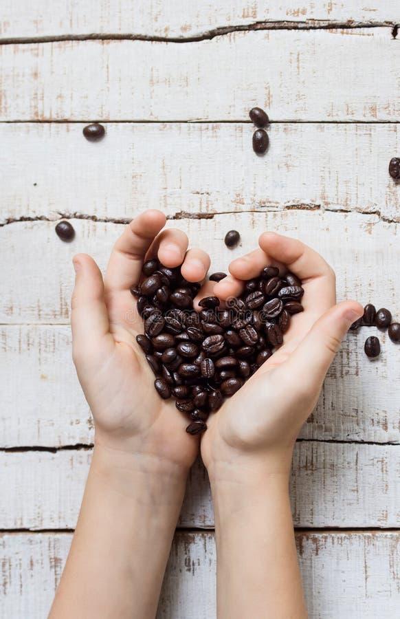 Cuore dei chicchi di caffè in mani fotografia stock libera da diritti