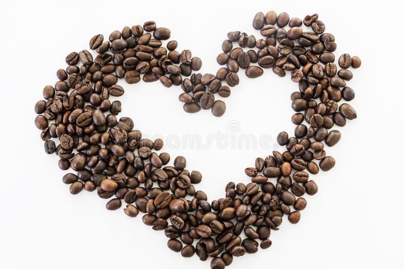 Cuore dei chicchi di caffè su un fondo bianco fotografie stock libere da diritti