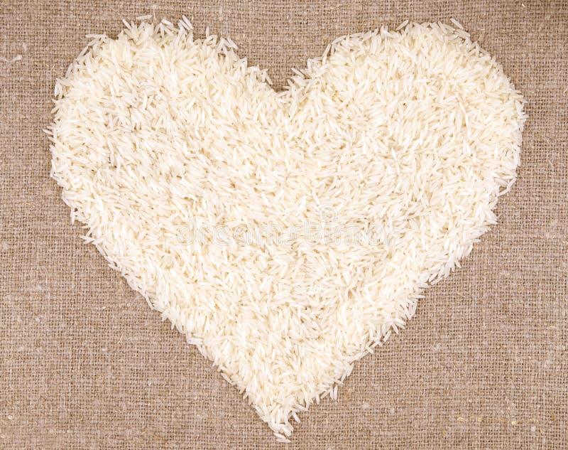 Cuore dei grani del riso su fondo di tela fotografia stock libera da diritti
