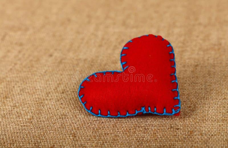 Cuore del mestiere del feltro di rosso sopra la fine della tela su fotografie stock
