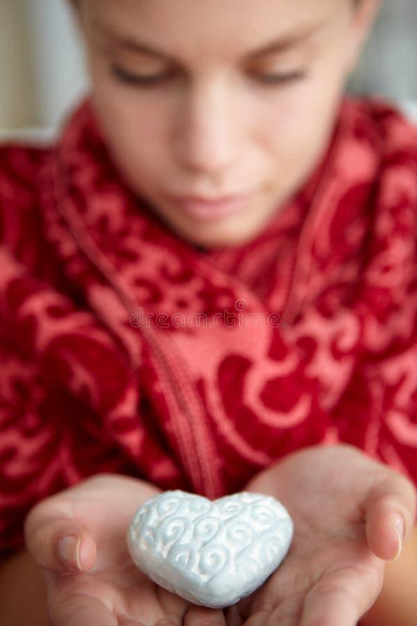 Cuore dell'argento della holding dell'adolescente fotografia stock