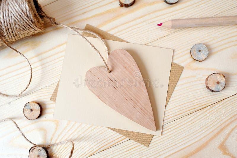 Cuore della carta kraft e di legno, posta con la matita su un fondo di legno Disposizione piana, derisione della foto di vista su fotografie stock libere da diritti