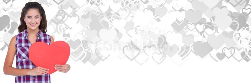Cuore della tenuta della donna dei biglietti di S. Valentino con il fondo dei cuori di amore fotografie stock