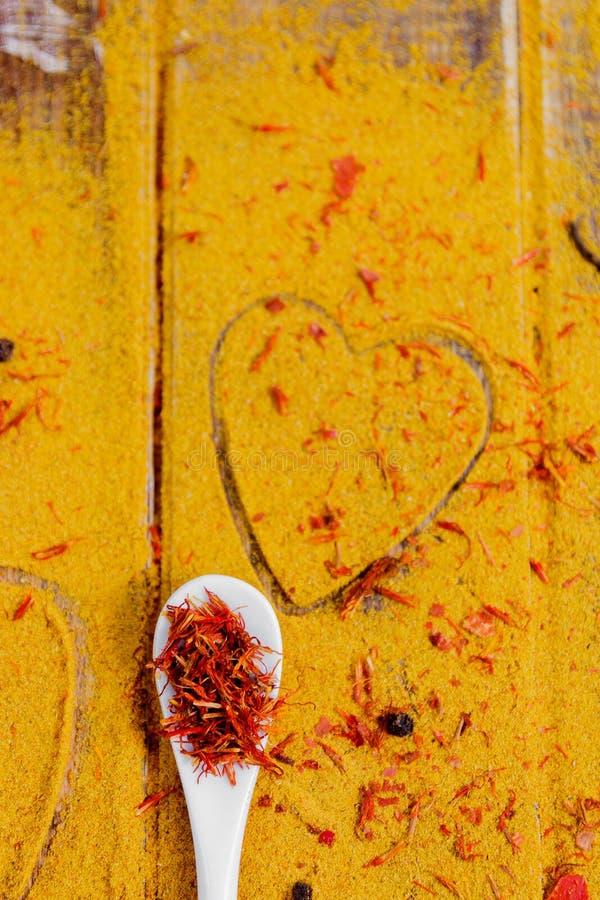 Cuore delle spezie e dei condimenti Cucchiaio bianco con zafferano sul fondo del curry Varia selezione closeup Copi lo spazio Amo fotografia stock