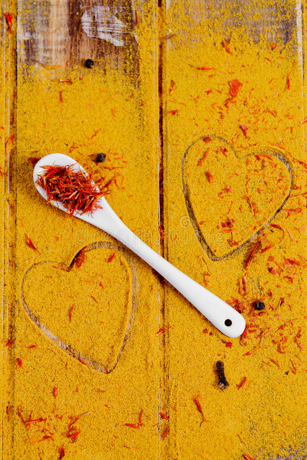 Cuore delle spezie e dei condimenti Cucchiaio bianco con zafferano sul fondo del curry Varia selezione closeup Copi lo spazio Amo immagine stock