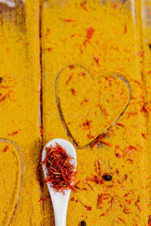 Cuore delle spezie e dei condimenti Cucchiaio bianco con zafferano sul fondo del curry Varia selezione closeup Copi lo spazio Amo immagine stock libera da diritti