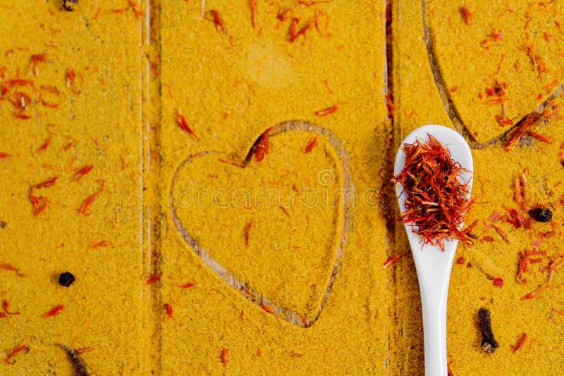 Cuore delle spezie e dei condimenti Cucchiaio bianco con zafferano sul fondo del curry Varia selezione closeup Copi lo spazio Amo fotografia stock libera da diritti