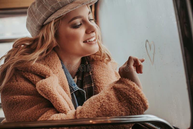Cuore di disegno di giovane signora felice sulla finestra immagine stock