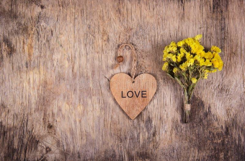 Cuore di legno e fiori gialli su un vecchio fondo di legno indossato Ambiti di provenienza e strutture Copi lo spazio immagini stock