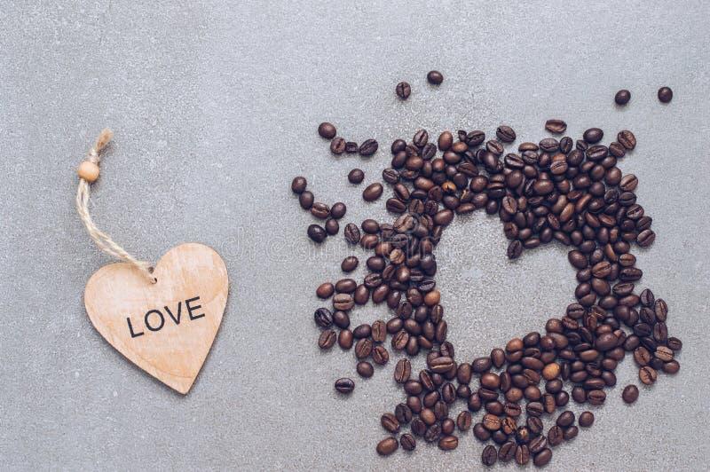 Cuore di legno e un cuore dei chicchi di caffè su un fondo grigio fotografie stock libere da diritti