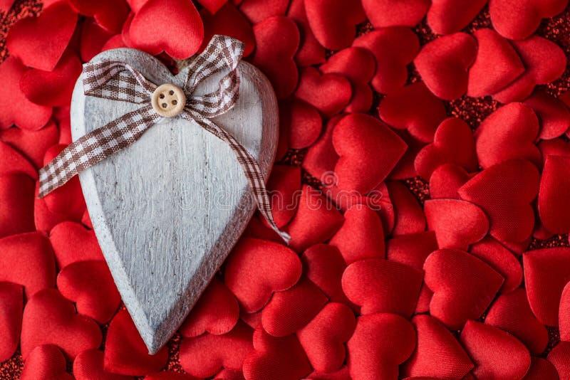 Cuore di legno sui piccoli cuori del raso, giorno di biglietti di S. Valentino, celebrante amore fotografie stock libere da diritti