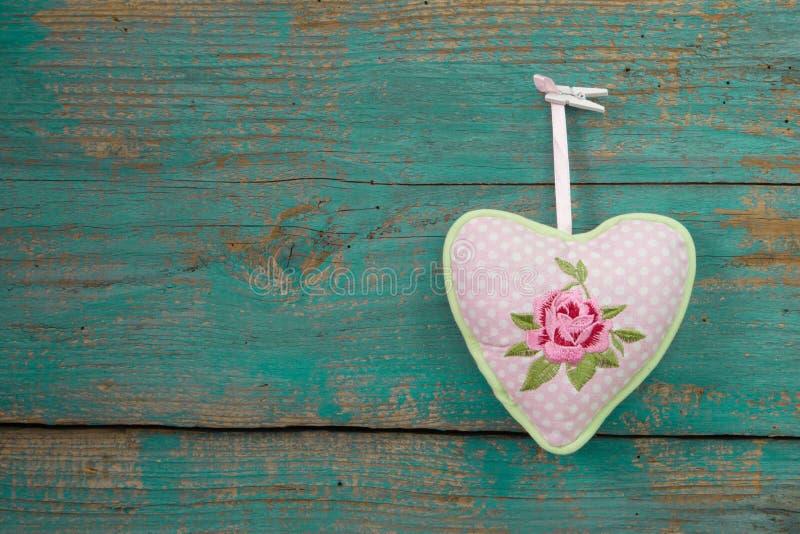 Cuore di Rosa con i punti e legno del turchese per un fondo del gr immagini stock
