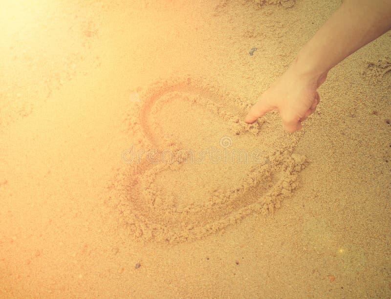 Cuore di tiraggio dell'uomo del muscolo sulla sabbia Luce e vinta internazionali del sole fotografia stock