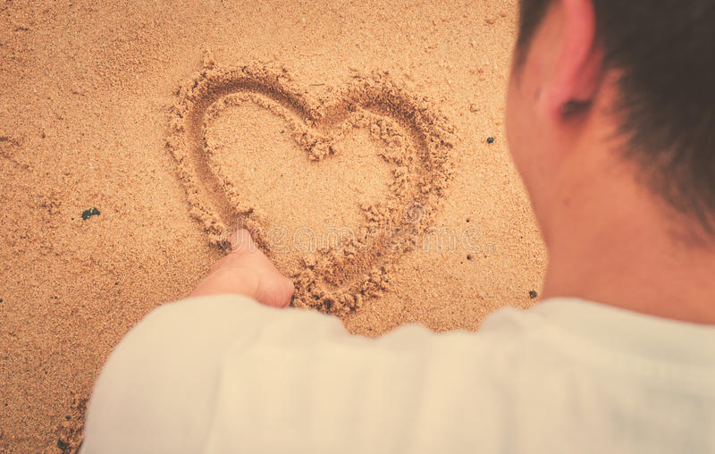 Cuore di tiraggio dell'uomo del muscolo sulla sabbia Luce e vinta internazionali del sole immagine stock