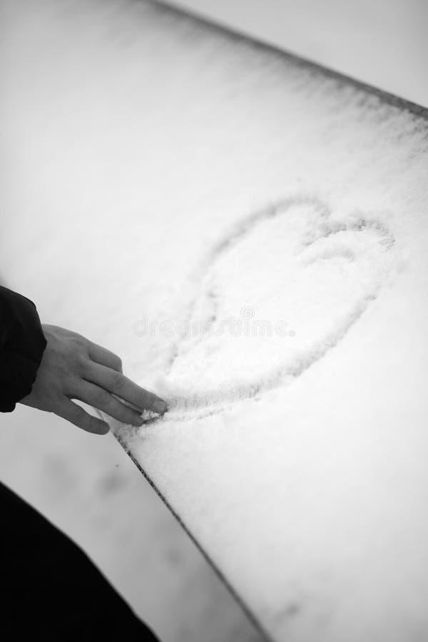 Cuore di tiraggio dell'uomo sul fondo della neve fotografie stock