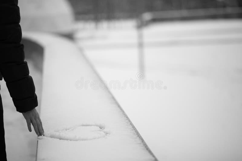 Cuore di tiraggio dell'uomo sul fondo della neve fotografia stock libera da diritti