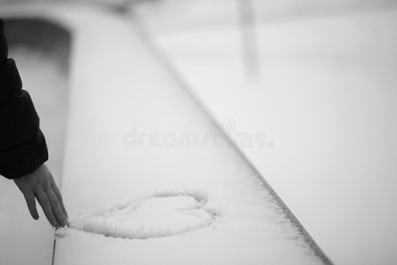 Cuore di tiraggio dell'uomo sul fondo della neve fotografie stock libere da diritti