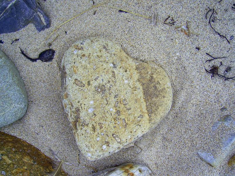 Cuore di una pietra sulla spiaggia immagine stock