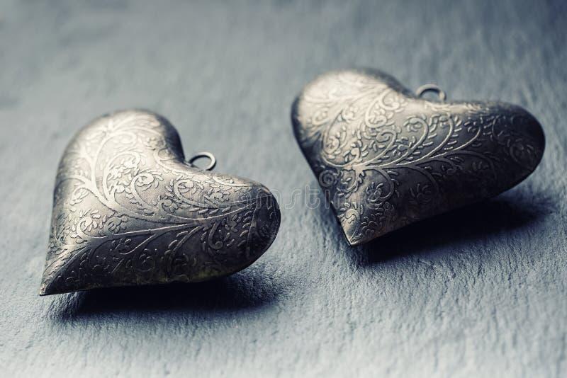 Cuore di Valentine Metal su un bordo del granito Il cuore d'argento del biglietto di S. Valentino due con gli ornamenti Cuore dei immagine stock libera da diritti