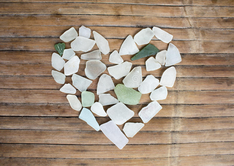 Cuore di vetro del ciottolo della spiaggia su fondo di legno Zuccheri il mosaico di vetro per il giorno del ` s del biglietto di  fotografia stock
