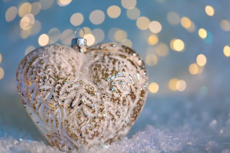 Cuore di vetro su una neve e fondo vago tonificato di colore di bokeh brillante con le luci d'ardore Decorazione di natale Copi l immagini stock