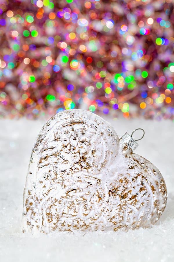 Cuore di vetro su una neve e fondo variopinto vago di bokeh brillante con le luci d'ardore Decorazione di natale Copi lo spazio immagine stock