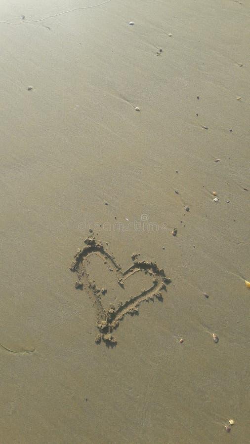 Cuore dissipato nella sabbia fotografia stock