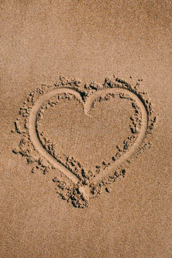 Cuore dissipato nella sabbia Fondo della spiaggia con il disegno del cuore Simbolo di amore di forma del cuore come fondo fotografia stock