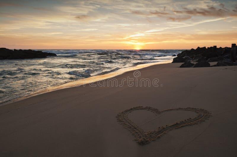 Cuore dissipato nella sabbia sulla spiaggia al tramonto immagini stock libere da diritti