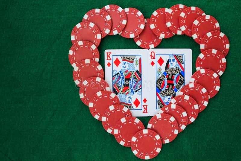 Cuore fatto con i chip di mazza, con re e la regina dei diamanti, su una tavola verde del fondo Vista superiore con lo spazio del fotografia stock