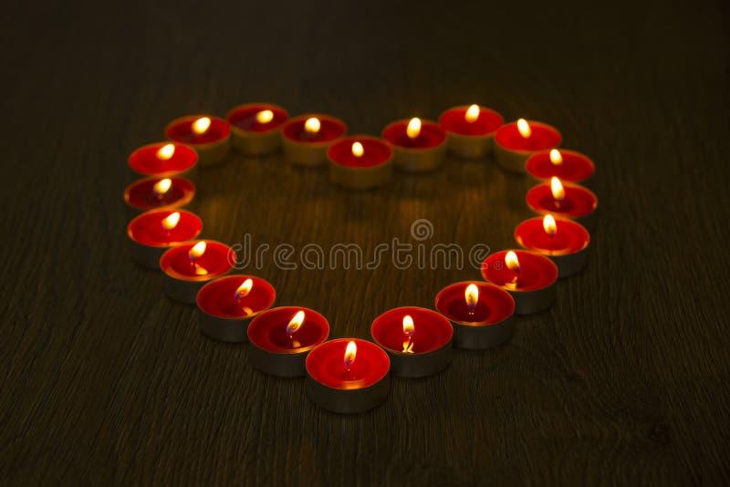 Cuore fatto con le candele rosse immagine stock