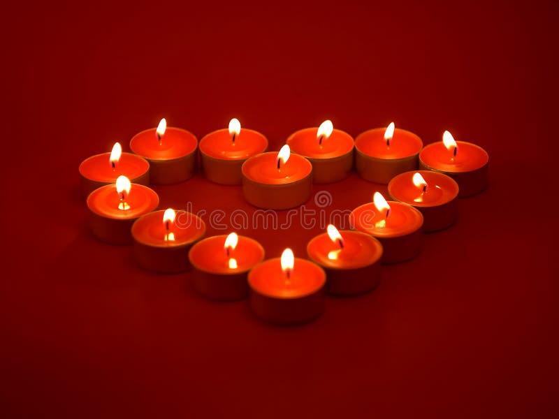 Cuore fatto dalle candele rosse su priorità bassa rosso scuro fotografia stock libera da diritti