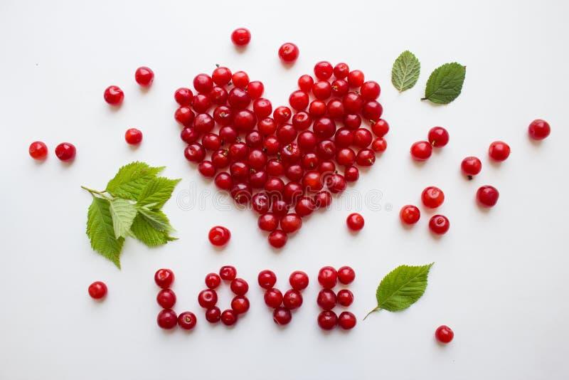 Cuore fatto dalle ciliege Le ciliege rosse su bianco sono allineate con l'amore di parola fotografia stock libera da diritti