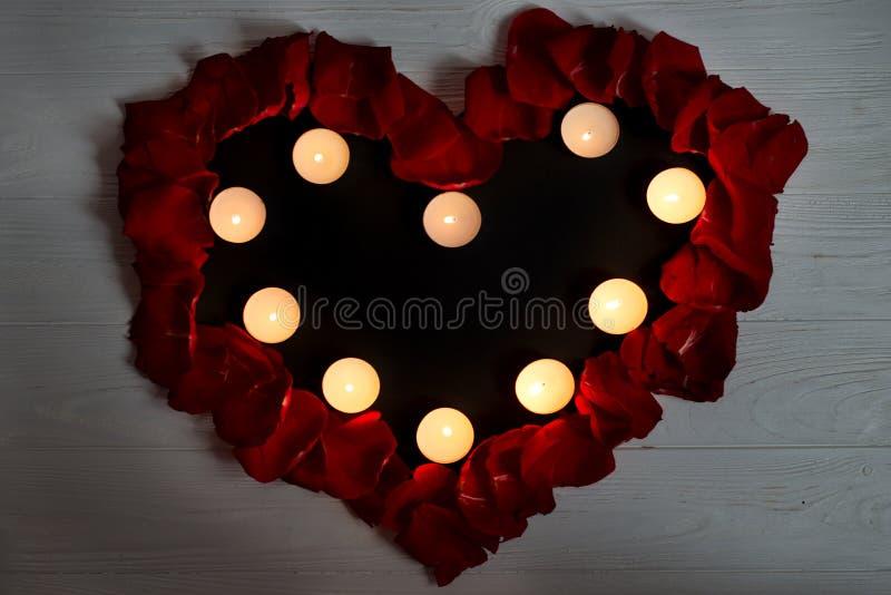 Cuore fatto dei petali rosa e delle candele brucianti su un fondo di legno Fondo di giorno del ` s del biglietto di S immagini stock libere da diritti